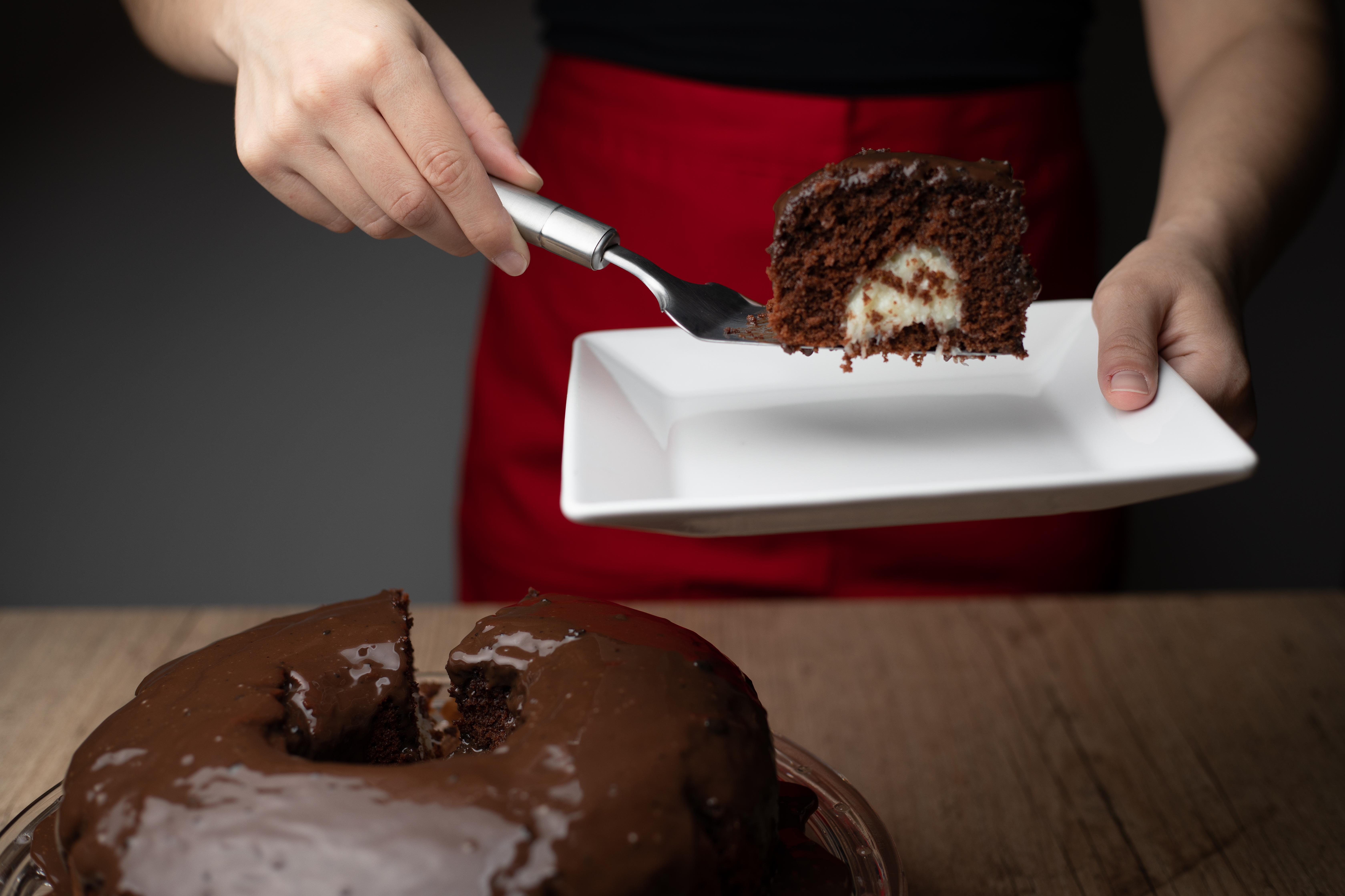 Bolo de chocolate com furo no meio coberto de brigadeiro à esquerda inferior da foto. À direita superior, pessoa com avental vermelho segurando prato e espátula com pedaço de bolo de chocolate com recheio de cocada ao centro.