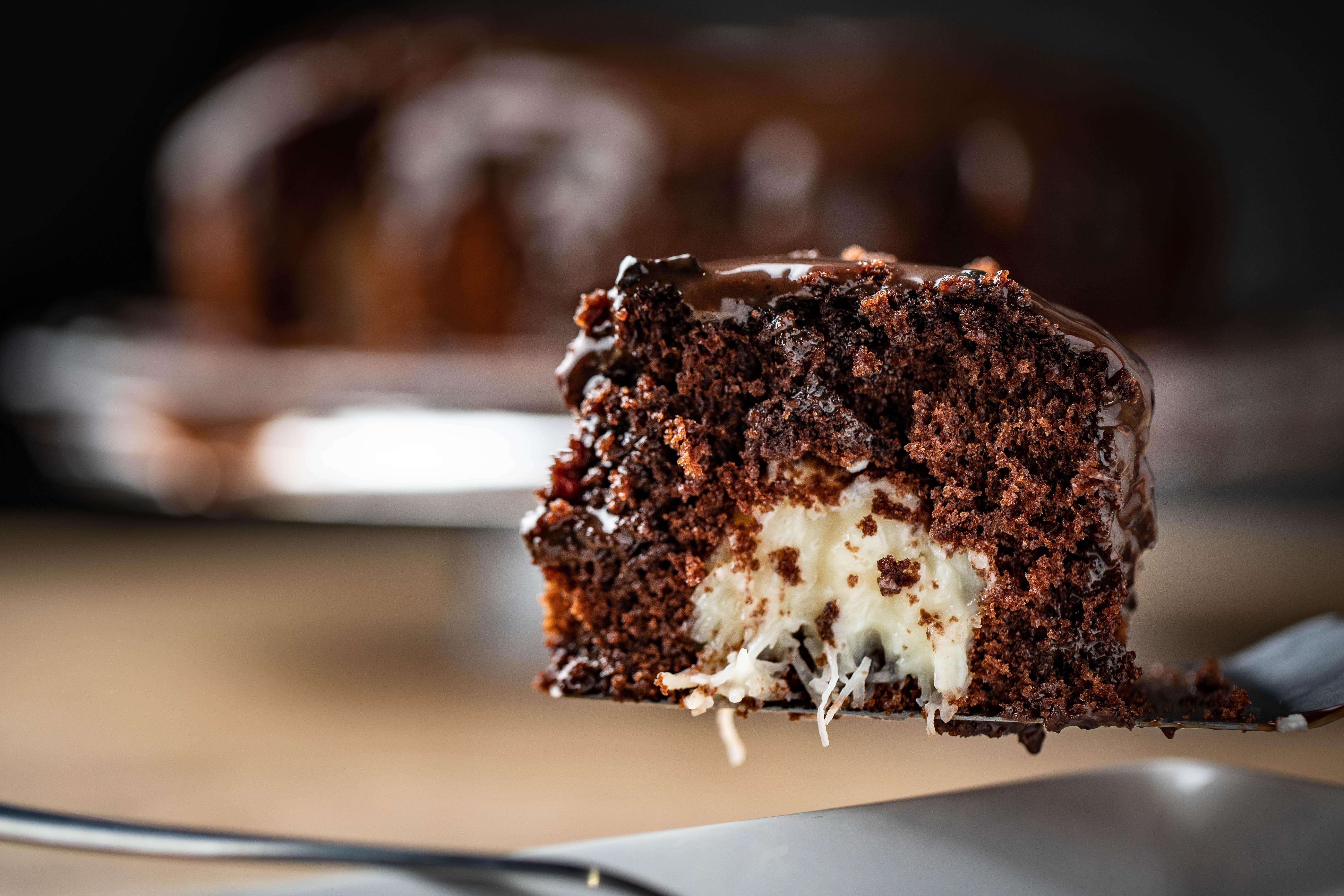 Pedaço de bolo de chocolate com recheio de cocada no centro e cobertura de brigadeiro sobre espátula e prato branco.